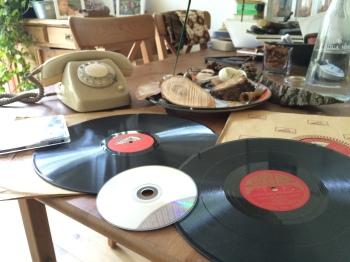 twee bakelieten grammofoonplaten op 78 toeren, eentje 12 en eentje 10 inch. Erboven op een CD